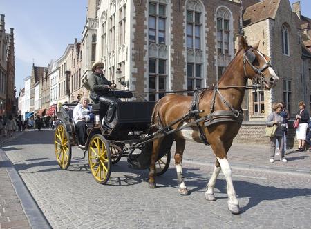 Brugge, België - 4 mei 2011: Paard en wagen met toeristen rijden door in Brugge, België op 04 mei 2011 Redactioneel