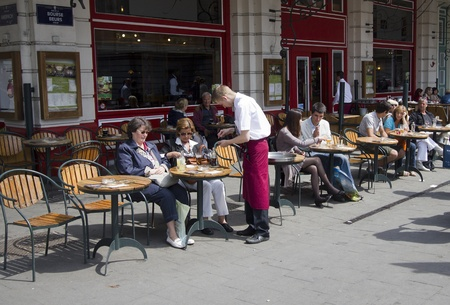 Brussels, Belgium - May 5, 2011: People pay the bill to a waiter on an outside cafe terrace on a street in downtown Brussels, Belgium on May 5, 2011.