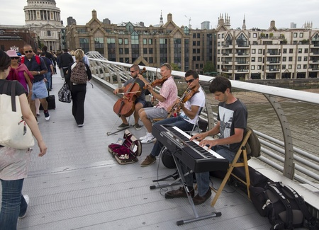 London, UK - July 25, 2011: Musicians play on Millennium Bridge in London on July 25, 2011 in London, UK