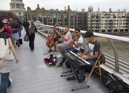 London, UK - July 25, 2011: Musicians play on Millennium Bridge in London on July 25, 2011 in London, UK Stock Photo - 13257378