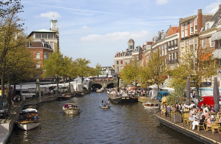 Leiden, Holland - September 24, 2011: People sitting at cafes along a canal in Leiden, Holland on September 24, 2011