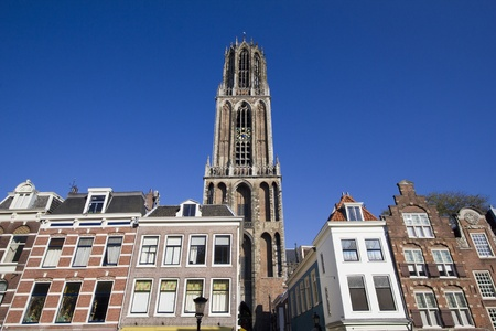 dom: The tower of the Dom cathedral above a row of historical houses of Utrecht, Holland Stock Photo
