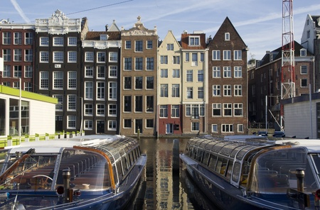 tour boats: Tour boats moored in a canal and historic houses in Amsterdam, Holland