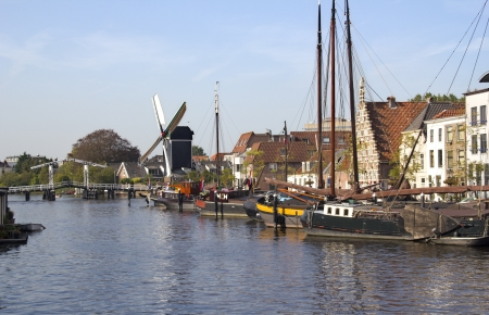 Boats, drawbridge and windmill along a canal in Leiden, Holland
