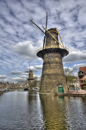 schiedam: Two large stone windmills on a canal in Schiedam, Holland