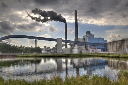 Factory with smoking chiney reflected in a pond photo