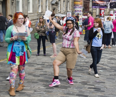 EDINBURGH, UK: AUGUST 2: Girls hand out flyers on the Edinburgh Festival Fringe in Edinburgh, UK on August 2, 2012