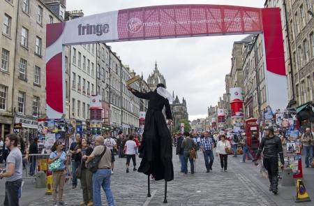 EDINBURGH, UK: AUGUST 2: Stilt walker passes under the Fringe Gate on the Royal Mile, the main street of Edinburgh, at the Edinburgh Festival Fringe on August 2, 2012 in Edinburgh.