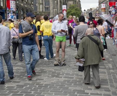 pantalones abajo: EDIMBURGO: 02 de agosto: El muchacho no identificado con los pantalones abajo reparte volantes en el Fringe Festival de Edimburgo el 2 de agosto de 2012 en Edimburgo Editorial
