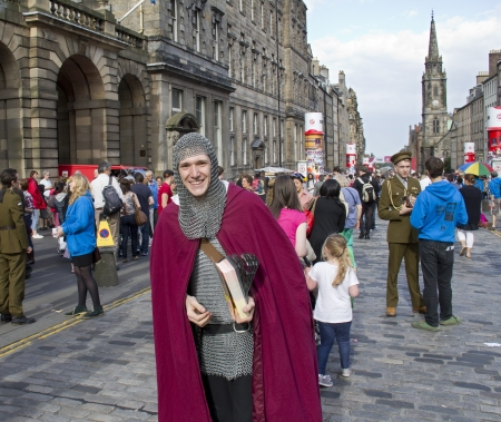 EDINBURGH, UK: AUGUST 2: Unidentified man dressed as a medieval knight hands out flyers on the street at the Edinburgh Festival Fringe in Edinburgh, UK on August 2, 2012