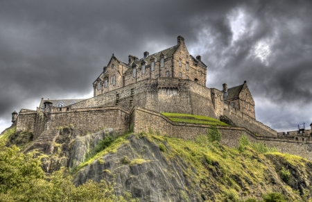 Edinburgh Castle on Castle Rock in Edinburgh, Scotland, UK against dark rainclouds