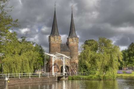 rainclouds: The Oostpoort gate in sunlight and dark rainclouds above in Delft, Holland Editorial