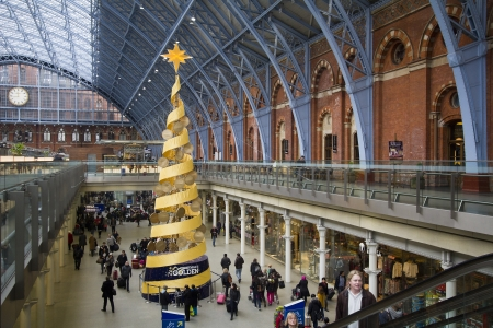pancras: London, UK - January 3, 2013: Large Christmas tree and travelers in St. Pancras Railway Station in London, UK on January 3, 2013