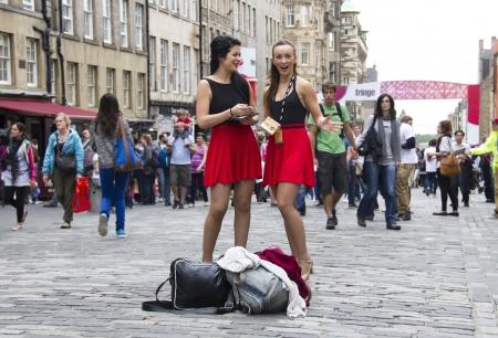 comedic: EDINBURGH, UK: AUGUST 2: Two girls hand out flyers on the street at the Edinburgh Festival Fringe in Edinburgh, UK on August 2, 2012