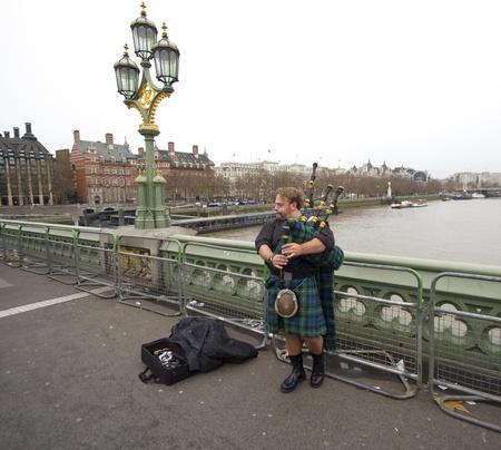 englishman: London, UK - December 28, 2011: Bagpipe player on Westminster Bridge on December 30, 2011 in London, UK Editorial