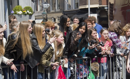 THE HAGUE, HOLLAND - MAY 3: Teenage fans of the boyband One Direction take pictures as the band leaves Hotel des Indes in The Hague, Holland on May 3, 2013