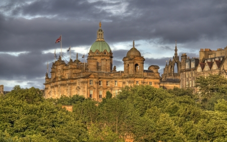 rainclouds: Buildings of old Edinburgh above the trees of Princes Street Gardens in the light of the setting sun