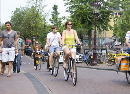 Amsterdam, Holland - July 19, 2013: Tourists on bikes cycle along a canal with trees on July 19, 2013 in Amsterdam, Holland Stock Photo - 21673934
