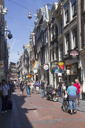 Amsterdam, Holland - July 19, 2013: Tourists walk in the red light district of Amsterdam on July 19, 2013 in Amsterdam, Holland