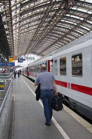 Cologne, Germany - August 30, 2013  Man with suitcase walking to his train on a platform in the historic railway station of Cologne, Germany on August 30, 2013