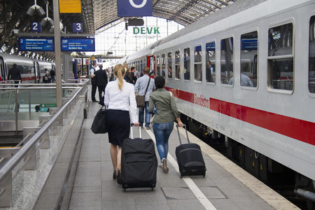 Cologne, Germany - August 30, 2013  People with luggage walk to an international train on a platform in the historic railway station of Cologne, Germany on August 30, 2013