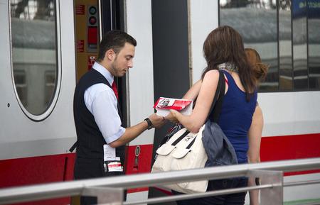 Keulen, Duitsland - 30 augustus 2013 Trein conducteur controleert de kaartjes van vrouwelijke reizigers op een internationale trein in het station van Keulen, Duitsland op 30 augustus 2013 Redactioneel