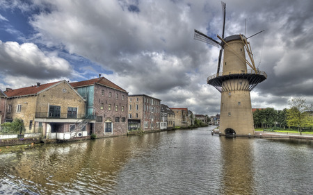 schiedam: Large stone windmill on a canal with historical warehouses in Schiedam, Holland