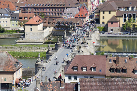 main river: Wurzburg, Germany - May 4, 2014: People cross the old Main Bridge across the Main river seen from above in Wurzburg, Germany on May 4, 2014