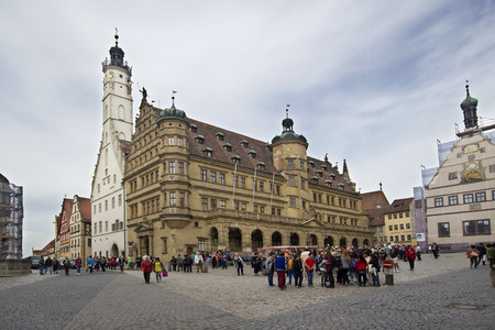 fachwerk: Rothenburg ob der Tauber, Germany - May 6, 2014: Groups of tourists walk on the medieval town square with city hall of Rothenburg ob der Tauber on May 6, 2014. Editorial