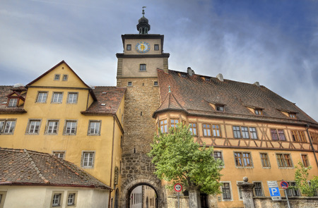 fachwerk: Ancient gate with clock tower and attached historical buildings in Rothenburg ob der Tauber, Germany Stock Photo