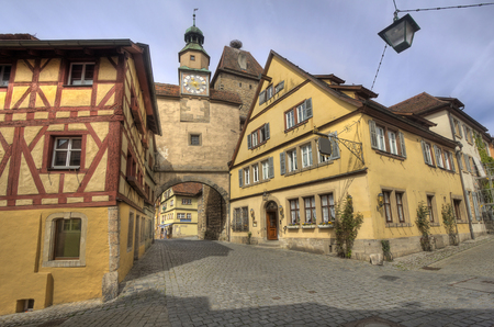 fachwerk: Historical street with ancient houses and hotels and an old gate and clock tower in Rothenburg ob der Tauber, Germany Editorial