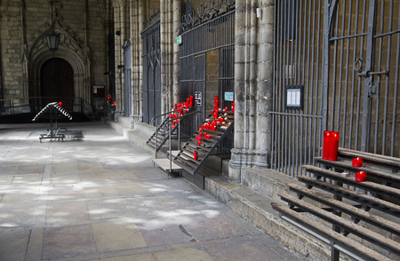 votive candle: Red votive candles in candle racks in front of the chapels in Barcelona Cathedral, Spain