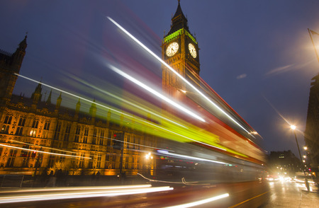 busses: Traffic of cars and busses drives by Big Ben at Westminster Parliament in London in the evening Stock Photo