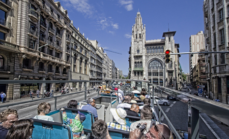 trafficlight: Barcelona, Spain - May 25, 2015: Tourists sit on the upper deck of a double decker bus touring around the city of Barcelona, Spain on May 25, 2015.