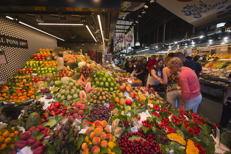 la boqueria: Barcelona, Spain - May 23, 2015: People buying fruit at a market stall in La Boqueria Market in Barcelona, Spain on May 23, 2015.