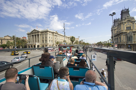 sit around: Barcelona, Spain - May 25, 2015: Tourists sit on a double decker bus touring around the city of Barcelona, Spain on May 25, 2015.