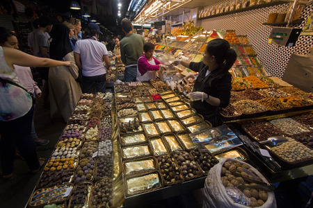 la boqueria: Barcelona, Spain - May 23, 2015: People buying nuts at a market stall in La Boqueria Market in Barcelona, Spain on May 23, 2015.