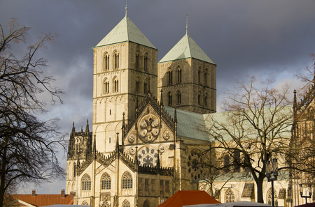 rainclouds: Saint Paulus Cathedral in Munster, Germany, in winter sunlight with dark rainclouds