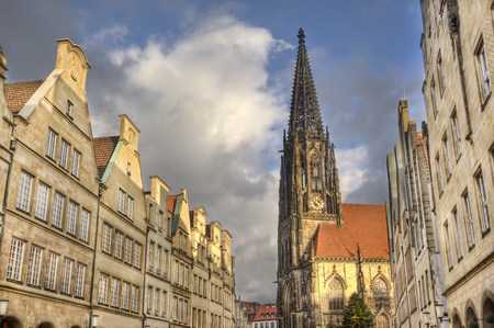 gables: Gables of historical houses and the tower of Saint Lamberti Church in the Prinzipalmarkt street in Munster, Germany Stock Photo