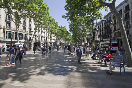 rambla: Barcelona, Spain - May 23, 2015: Tourists and local people walk and sit on benches on the famous La Rambla street in downtown Barcelona, Spain on May 23, 2015. Editorial