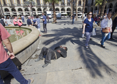 passed out: Barcelona, Spain - May 28, 2015: Drunk person has passed out on plaza in central Barcelona, on May 28, 2015 in Barcelona, Spain Editorial