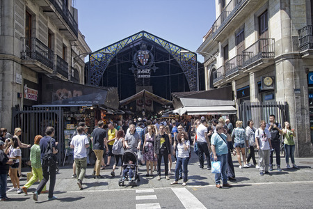 buidings: Barcelona, Spain - May 23, 2015: Tourists at the entrance to La Boqueria Market in Barcelona, Spain on May 23, 2015.