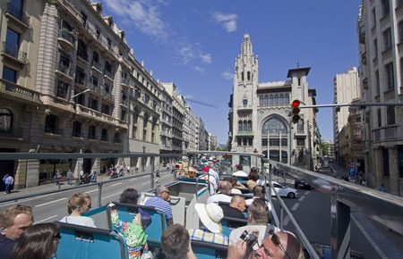 sit around: Barcelona, Spain - May 25, 2015: Tourists sit on the upper deck of a double decker bus touring around the city of Barcelona, Spain on May 25, 2015.