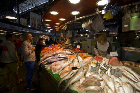 ramblas: Barcelona, Spain - May 23, 2015: People buying fish at a market stall in La Boqueria Market in Barcelona, Spain on May 23, 2015.