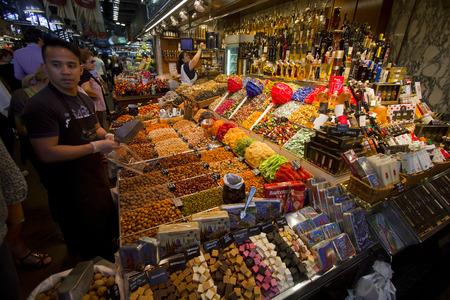 la boqueria: Barcelona, Spain - May 23, 2015: Man selling nuts and candy at a market stall in La Boqueria Market in Barcelona, Spain on May 23, 2015. Editorial