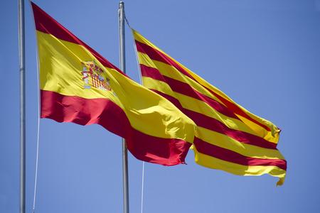 autonomia: Español y catalán bandera volando juntos contra el cielo azul en un edificio de un banco en Barcelona, ??España