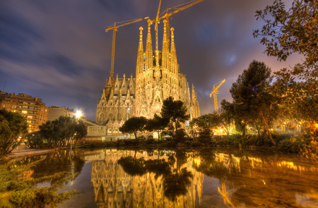 Sagrada Familia cathedral under construction seen across a pond in the evening in Barcelona, Spain
