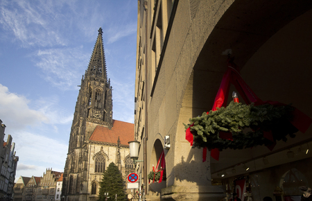 guirnaldas navide�as: Christmas wreaths outside shops and a christmas tree in front of Saint Lamberti Church in  Munster, Germany