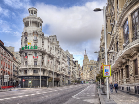 streetlife: Madrid, Spain - May 28, 2016: People walk along the magnificent architecture of the Gran Via main street of Madrid, Spain on May 28, 2016