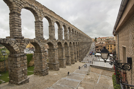 Segovia, Spain - May 30, 2016: People walk beneath the ruins of the roman aquaduct in Segovia, Spain on May 30, 2016 Editorial